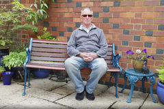 Man sitting on a bench. In his garden Stock Photos