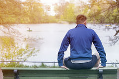 Man sitting on bench and looking at a lake Stock Photos