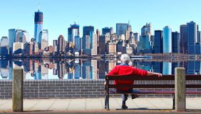 Man sitting on bench Manhattan skyline. Elderly man sitting on a bench in front of lower Manhattan skyline.  New York city Royalty Free Stock Image