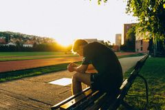 Man Sitting on Bench Near Track Field While Sun Is Setting stock photo