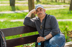 Man sitting on a bench in a park at sunny spring day Stock Photography