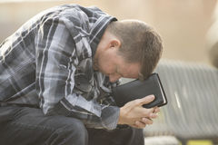 Man sitting on bench and praying with Bible. Close to face Royalty Free Stock Images