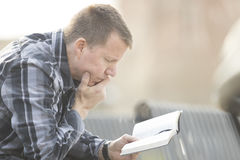 Man sitting on bench and reading bible stock photos
