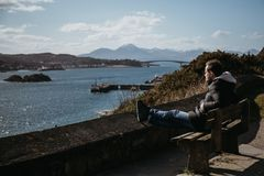 Man sitting on a bench, relaxing in the sun in Kyle of Lochalsh, Scotland. Skye Bridge and Isle of Skye on the background stock image