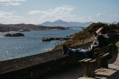 Man sitting on a bench, relaxing in the sun in Kyle of Lochalsh, Scotland. Skye Bridge and Isle of Skye on the background royalty free stock photo