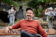 Man sitting on bench. Smiling handsome young man sitting on bench in the park and some tourist on background Stock Images