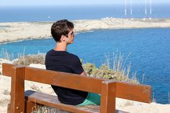 Young Man sitting on bench on sunny day and looking to ocean and sky horizon. Man relaxing under hot sun and after day walking. royalty free stock photos
