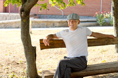 Man sitting on a bench in a sunny day of summer Royalty Free Stock Image