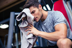 Man sitting on the bench with towel. Portrait of a handsome man sitting on the bench with towel in fitness gym stock images
