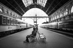 Man Sitting on Bench in Train Station in Grayscale Photography Royalty Free Stock Photography