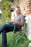Man sitting on bench using a digital tablet Royalty Free Stock Photos