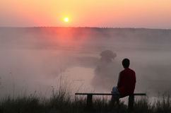 Man sitting on bench and watching misty sunrise. Rear view of a man sitting on bench and watching misty sunrise Stock Images