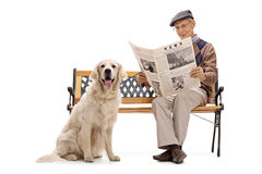 Man sitting on a bench wth his dog and reading Stock Image