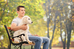 Man sitting on bench with a young dog Stock Photo
