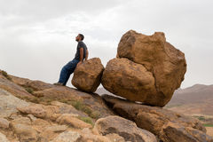 Man sitting on big rocks on the edge of a mountain. Man leaning on round big rocks on a desert mountain. Photo from south of Morocco near Tinghir city Stock Photos