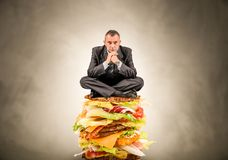 Man sitting on a big sandwich Stock Image