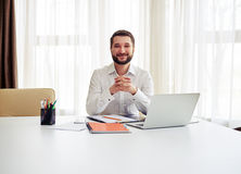 Man sitting at the big white table and crossed his fingers in th Stock Photography