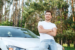 Man sitting on bonnet with crossed arms Stock Images