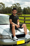 Man sitting on bonnet of silver car in countryside Stock Image