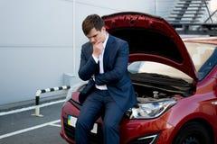 Man sitting on bonnet upset because of broken car Stock Images