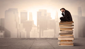 Man sitting on books in the city Royalty Free Stock Photo