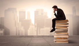 Man sitting on books in the city Royalty Free Stock Image