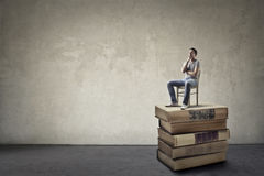 Man sitting on books Royalty Free Stock Images