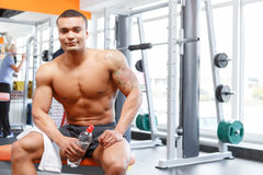 Man sitting with bottle and towel in gym Royalty Free Stock Photo