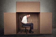 Man sitting in a box working on laptop Royalty Free Stock Photography