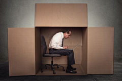 Man sitting in a box working on laptop computer Royalty Free Stock Photos