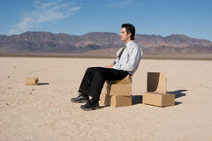 Man sitting on boxes Stock Image