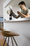 Man sitting at breakfast bar in kitchen with cafetiere and mug, reading newspaper, low angle view Stock Image