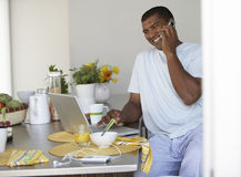 Man sitting at breakfast table in kitchen, using laptop and mobile phone, smiling, side view Royalty Free Stock Photography