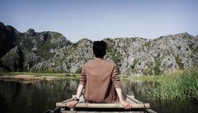 Man Sitting on Bridge Front of Mountain Stock Image