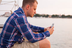 Man sitting on the bridge next to sea and using tablet. Stock Photo