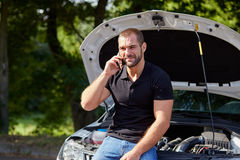 Man sitting on a broken car Royalty Free Stock Photography
