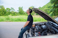 Man sitting on a broken car waiting for assistance Stock Images