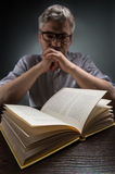 Man sitting at brown table and reading book. Royalty Free Stock Photo