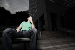 Man sitting by a building Royalty Free Stock Image