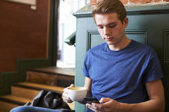 Man Sitting In Caf� and Checking Messages On Mobile Phone Stock Photo