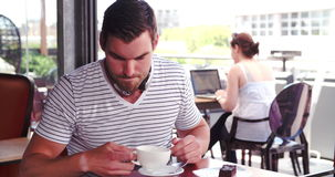 Man Sitting In Cafe With Digital Tablet Listening To Music. Man sitting at table in coffee shop puts on headphones and chooses music from digital tablet.Shot in stock video