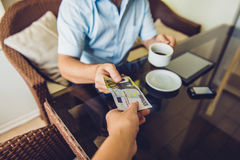 Man sitting in the cafe gives money to another man Stock Photography