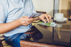Man sitting in the cafe gives money to another man Royalty Free Stock Photo