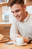 Man sitting in cafe while listening music and drinking coffee. Stock Photography