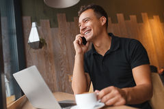 Man sitting in cafe with phone, laptop and coffee Stock Images