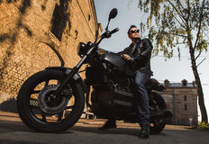 Man sitting on a cafe-racer motorcycle. Outdoors stock images
