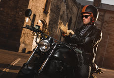 Man sitting on a cafe-racer motorcycle royalty free stock image