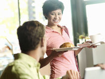 Man sitting at cafe table, focus on young woman carrying cup and plate in background, smiling Stock Images