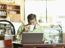 Man sitting at cafe table, using laptop, drinking mug of coffee, front view, portrait Royalty Free Stock Photography