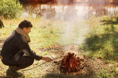 Man sitting at campfire Stock Photography